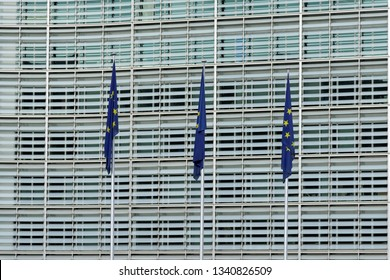 BRUSSELS, BELGIUM - AUGUST 16, 2018: Row of EU Flags in front of the European Union Commission building in Brussels.