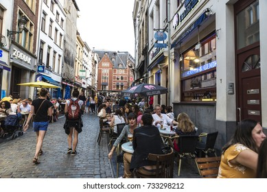 Brussels, Belgium - August 26, 2017: People in a bar having a drink and walking on a street in Brussels, Belgium