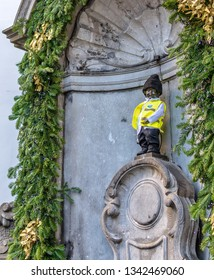 Brussels, Belgium - December 13, 2018:  Manneken Pis (Little Pisser) dressed in yellow vest and black hat. Bronze sculpture depicting naked little boy urinating into a fountain's basin.