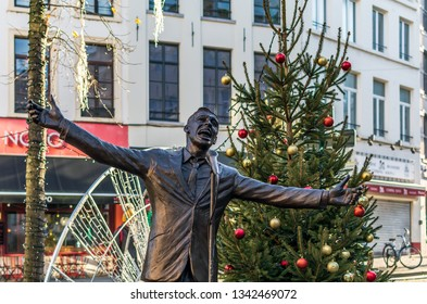 Brussels, Belgium - December 13, 2018: Statue of Jacques Brel and Christmas tree. Bronze statue entitled L'envol (The Flight) shows singing Brel behind his microphone with his arms wide open.