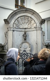BRUSSELS, BELGIUM - FEBRUARY 20, 2019: Group of tourists gathering around the famous statue Manneken Pis in the center of Brussels, the capital of Belgium.