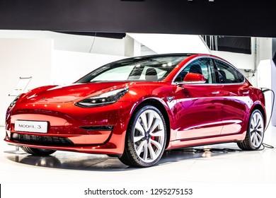 Brussels, Belgium, Jan 18, 2019: metallic red Tesla Model 3 at Brussels Motor Show, produced by American automaker Tesla, main shareholder Elon Musk