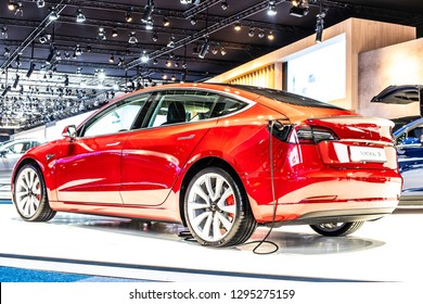 Brussels, Belgium, Jan 18, 2019: metallic red Tesla Model 3 at Brussels Motor Show, produced by American automaker Tesla, main shareholder Elon Musk