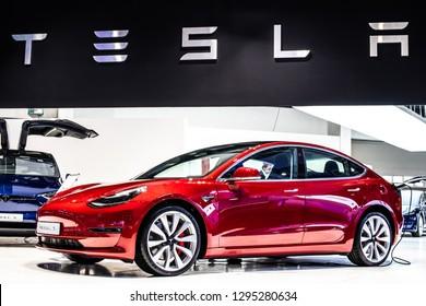 Brussels, Belgium, Jan 18, 2019: metallic red Tesla Model 3 and blue Tesla model X at Brussels Motor Show, produced by American automaker Tesla, main shareholder Elon Musk,