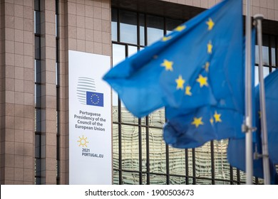 Brussels, Belgium - January 22, 2021: European flags fluttering in the wind in front of the European Council with the logo of the Portuguese rotating presidency