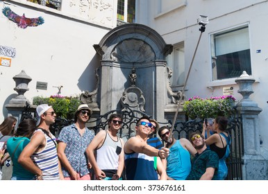 BRUSSELS, BELGIUM - JULY 10, 2015: Unknown american tourists making a selfie in front of Manneken Pis statue, one of the most famous Belgian and Brussels monuments and a symbol of the city