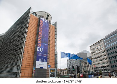 """BRUSSELS, Belgium -july 1st, 2020: European flags in the wind in front of The """"Next Generation EU"""" banner on the front of the Berlaymont building, the headquarters of the European Commission"""