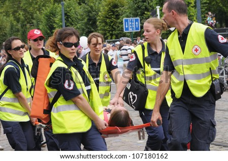BRUSSELS, BELGIUM - JULY, 21: Belgian Red Cross team helps to person with sunstroke during National Day of Belgium on July 21, 2009 in Brussels. Well trained and equipped teams were on duty this day