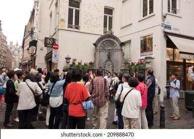 BRUSSELS, BELGIUM - JULY 24, 2014: Tourists visiting the Manneken pis ( Little Man Pee or le Petit Julien) an iconic symbol of the Belgian Capital