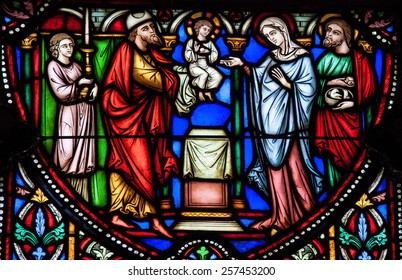 BRUSSELS, BELGIUM - JULY 26, 2012: Stained Glass window depicting Simeon the Godreceiver, who met the Child Jesus in the Temple in Jerusalem, located in the Cathedral of Brussels, Belgium.