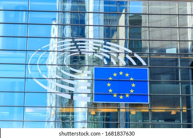 Brussels, Belgium - July 3, 2019: Symbol of the European Parliament and the flag of the European Union over the entrance to the buildings of the European Parliament