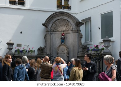 Brussels, Belgium - June 24, 2018 : Tourists taking photos at Manneken Pis (Little man Pee), a landmark small bronze sculpture in Brussels, wearing the costume of the City of Montreal