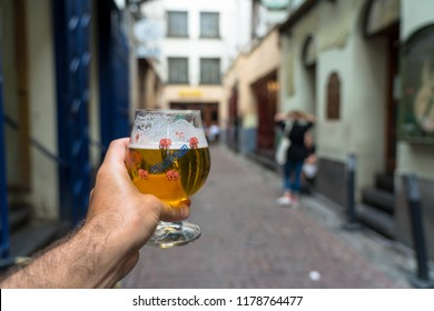 BRUSSELS, BELGIUM - JUNE 7, 2018: Hand holding glass of beer from Delirium Cafe, well known for a long beer list, standing at 2,004 brands as recorded in the Guinness Book of Records.
