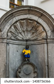 BRUSSELS, BELGIUM - MARCH 11 2019: Manneken Pis is a famous bronze sculpture in Brussels. His wardrobe includes hundreds of different costumes, including sports outfits like this blue and yellow one.