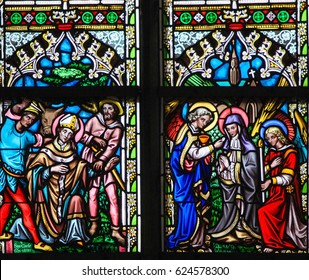 BRUSSELS, BELGIUM - MARCH 13, 2017: Stained Glass in the Church of Our Blessed Lady of the Sablon in Brussels, Belgium, depicting two Catholic Saints and heraldic symbols
