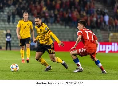 Brussels, Belgium - March 21, 2019. Belgium national team captain Eden Hazard against Russia midfielder Aleksandr Golovin during UEFA Euro 2020 qualification match Belgium vs Russia in Brussels.