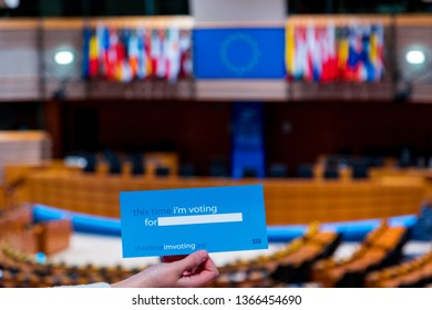 Brussels, Belgium - March 4, 2019: Holding a voting card in the empty European Parliament Assembly Room, where members of the EP vote to pass laws in the European Union (EU)