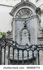 BRUSSELS, BELGIUM - MAY 11, 2014: The Mannekin Pis (le Petit Julien, designed by Hieronymus Duquesnoy the Elder, 1618 or 1619), is a famous statue a naked little boy urinating into a fountain's basin.