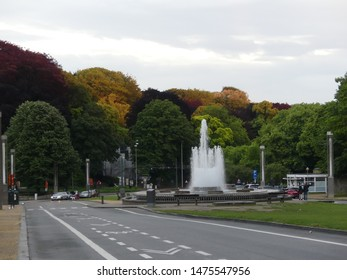 Brussels, Belgium - May 2019: Fountain on the background of colorful trees in a park near the Atomium, an iconic building in Brussels.