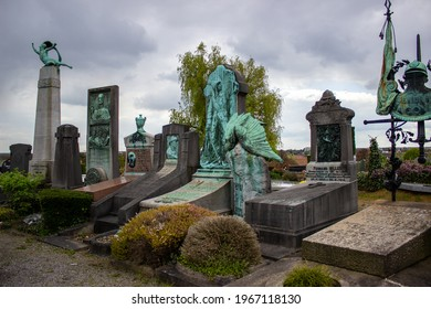 Brussels, Belgium; May 2nd, 2021: stone tombs at the Ixelles cemetery in a cloudy day. Green grass and beautiful teal sculptures decorating the graveyard.