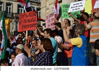BRUSSELS, BELGIUM - MAY 7, 2011: People wave Syrian flags and shout slogans during a protest against Syrian President Bashar Assad in Brussels