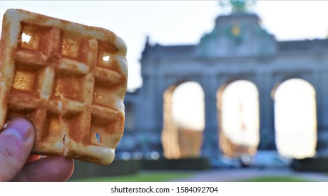 Brussels, Belgium. November 2019. Close up of a Brussels Gaufre. In the background, the fiftieth anniversary building.