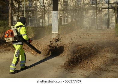 Brussels, Belgium - November 29, 2016: Side view of a professional in fluorescent suit with a leaf blower, blowing autumn leaves in the Cinquantenaire park.
