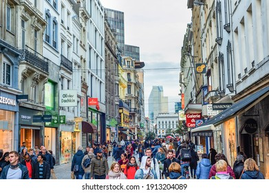 BRUSSELS, BELGIUM - OCTOBER 5, 2019: Central shopping street crowded with tourists, downtown architecture, evening cityscape view