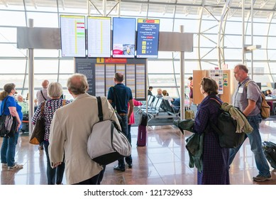 Brussels / Belgium - September 16 2018:  People looking at the departures board in Brussels airport in Belgium. Group of travelers checking arrivals board. Travel concept.