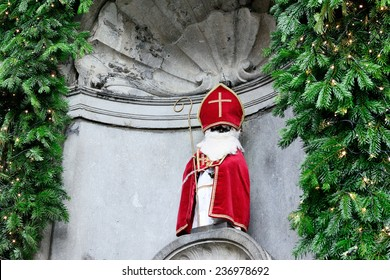 BRUSSELS, BELGIUM-DECEMBER 6, 2014: Manneken Pis received costume of Saint Nicolas in day of parade of Saint Nicolas in historical center of the city