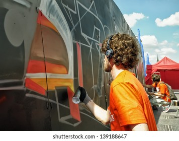 BRUSSELS, BELGIUM-MAY 5: Unidentified graffitists paint on a wall during annual Day of Iris - Fete de l'Iris on May 5, 2013 in Brussels.