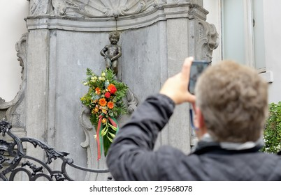 BRUSSELS, BELGIUM-SEPTEMBER 21, 2013: Manneken Pis with flowers prepared for a ceremony of award of costume and a tourist taking his picture