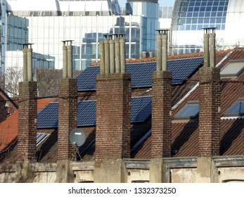 BRUSSELS - FEBRUARY 25: Solar panels and old chimneys on a house. Depicts the concept of energy transition from dirty fossil fuels to clean energy.Photo taken on February 25, 2018 in Brussels, Belgium