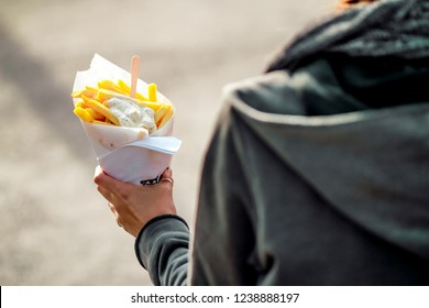 Brussels, Kingdom of Belgium. Tourist holds belgian fries in hand in the streets of Brussels. French Fries with mayonnaise.