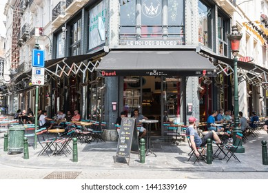 Brussels Old Town / Belgium - 06 25 2019: Young people having a drink on a sunny terrace at Le Roy Des  Belges at the Saint Géry quarter during a hot summer day