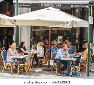 Brussels Old Town / Belgium - 06 25 2019: People of all ages and mixed gender sitting on a sunny terrace of the brasserie restaurant Les gens que j'aime - the people I love