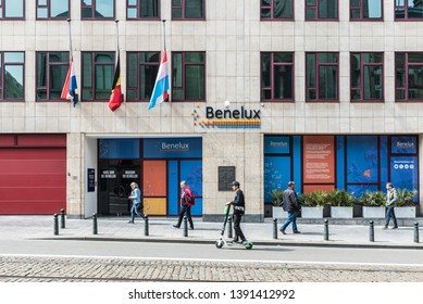Brussels Old Town, Brussels Capital Region / Belgium - 05 01 2019: People walking and driving an electronic step in front of the Benelux secretary general facade