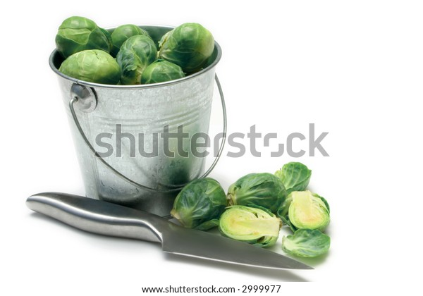 Brussels Sprouts in galvanized bucket with knife on white