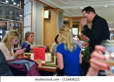 Brussels/Belgium- 03/19/2012: A group of teenage girls argue with a frustrated, older waiter about the total of their bill.