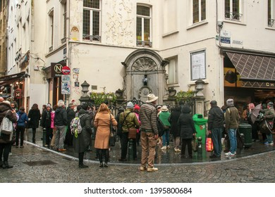 Brussels/Belgium; 04/29/2016. Tourists visiting the famous Statue Manneken Pis in Brussels. Statue dressed in traditional costume.
