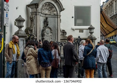 Brussels/Belgium - April 1, 2019: Tourists taking pictures and standing near one of the symbols of Brussels - Manneken Pis - The peeing boy statue