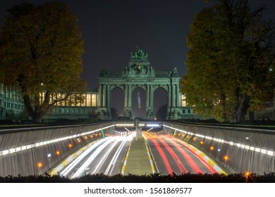 Brussels/Belgium - November 2019: The Triumphal arch in the Park of the Fiftieth Anniversary in Brussels and street traffic at night