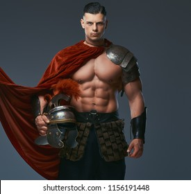 Brutal ancient Greece warrior with a muscular body in battle uniforms holds a helmet while standing in a studio.