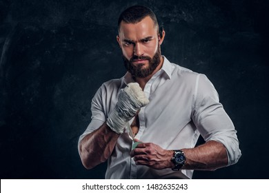 Brutal angry man in white shirt is wearing protection on his fist before fight at dark studio.