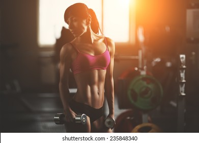 Brutal athletic fitness woman pumping up muscles with dumbbells. Brunette sexy fitness girl in pink sport wear with perfect body in the gym posing before training set. Attractive fitness woman