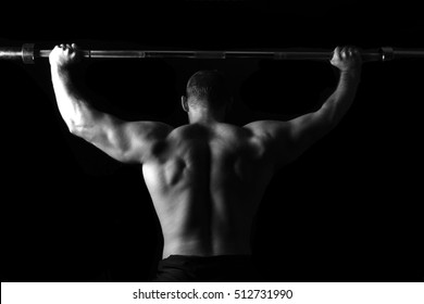 Brutal athletic man pumping up muscles on bench press in monochrome. Bodybuilder. Naked to the waist. Black and white photography. Sport. Low key. Gym. Isolated on black.