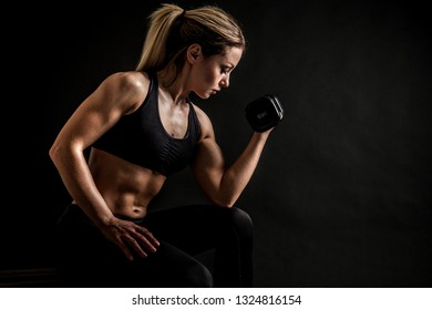 Brutal athletic woman pumping up muscles with dumbbells
