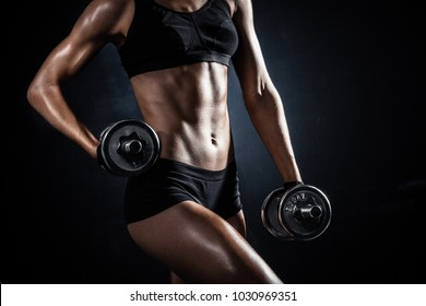 Brutal athletic woman torso pumping up muscles with dumbbells