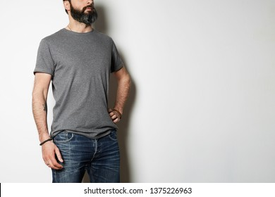 Brutal attractive bearded biker man with tattooed hands poses in gray blank t-shirt from premium thin cotton, on white mockup background