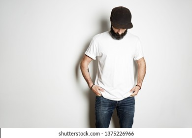 Brutal attractive bearded biker man with tattooed hands poses in white blank t-shirt from premium thin cotton, on white mockup background
